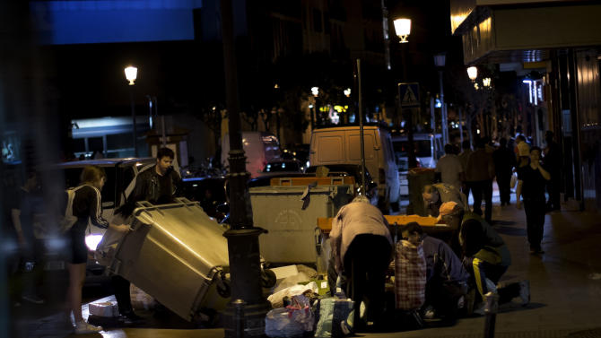 People look for food in a trash bin in Madrid, Wednesday, April 17, 2013. Many stores throw out food when they close every night and people often gather to look though the garbage bins. Spanish Prime Minister Mariano Rajoy has brushed off dismal economic predictions from the International Monetary Fund that the country's economy will continue shrinking in 2013. (AP Photo/Daniel Ochoa de Olza)