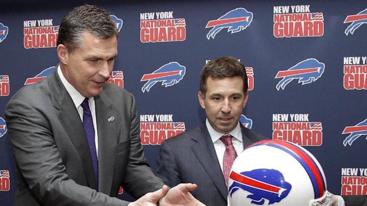 Buffalo Bills coach Doug Marrone, left,  is handed a Bills helmet for a photo opportunity with Bills president Russ Brandon, right, after being introduced as the new head coach after an NFL football news conference in Orchard Park, N.Y., Monday, Jan. 7, 2013. (AP Photo/David Duprey)