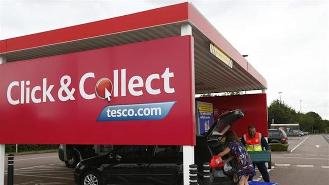 A worker helps a customer load her car with groceries at a Tesco click and collect point in Leicester, central England, August 29, 2013. REUTERS/Darren Staples/Files