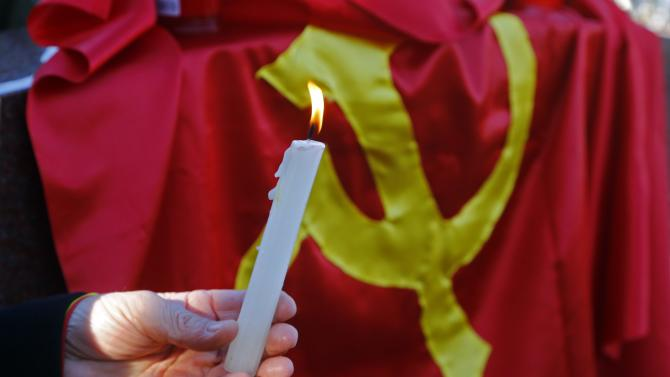 A man holds a candle during a commemoration ceremony at Romania's late communist dictator Nicolae Ceausescu grave in a Bucharest cemetery