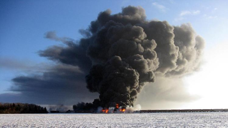 This photo provided by Cass County Commissioner Ken Pawluk shows a train derailment and fire west of Casselton, N.D., Monday, Dec. 30, 2013. No one has been reported hurt in the derailment or fire. By late Monday afternoon, the smoke plume was diminishing and was staying mostly away from town. (AP Photo/Ken Pawluk)