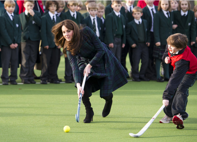 Kate, the Duchess of Cambridge, centre,  plays hockey during her visit to St. Andrew's School, where she  attended school from 1986 till 1995, in Pangbourne, England, Friday, Nov. 30, 2012. The Duches