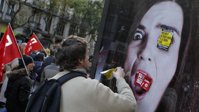 """A protestor places flyers reading, """"general strike"""" and """"you don't need to pay anything, they owe you everything"""" during a general strike in Madrid, Spain, Wednesday, Nov. 14, 2012. Spain's main trade unions stage a general strike, coinciding with similar work stoppages in Portugal and Greece, to protest government-imposed austerity measures and labor reforms. The strike is the second in Spain this year. (AP Photo/Andres Kudacki)"""