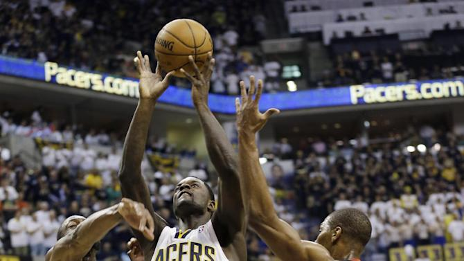Indiana Pacers' Lance Stephenson, center, puts up a shot between Miami Heat's Dwyane Wade (3) and Chris Bosh during the second half of Game 3 of the NBA Eastern Conference basketball finals in Indianapolis, Sunday, May 26, 2013. (AP Photo/Nam H. Huh)
