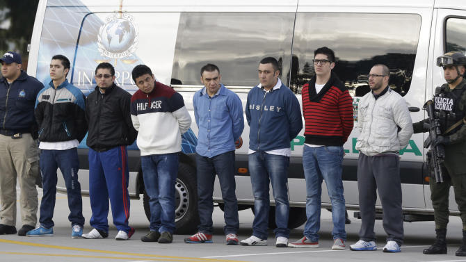 """Police flank seven men accused of murdering a Drug Enforcement Administration agent, during a media presentation at the counter-narcotics base in Bogota, Colombia, Tuesday, July 1, 2014, prior to their extradition to the United States. The men are accused of killing Special Agent James """"Terry"""" Watson in an apparent robbery attempt the night of June 20, 2013. (AP Photo/Fernando Vergara)"""