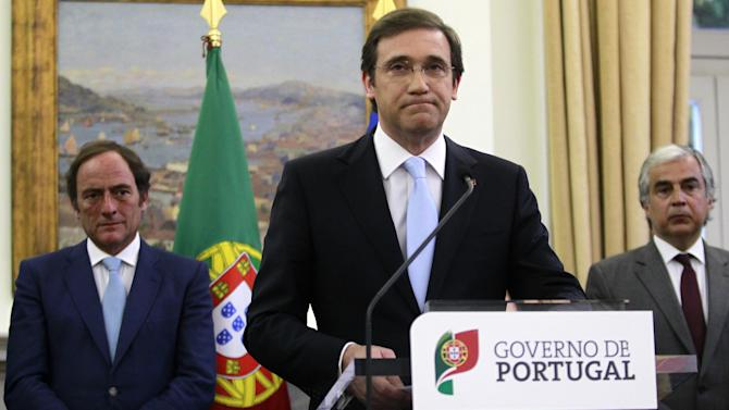 Portugal's Prime Minister Pedro Passos Coelho, center, addresses a statement to the nation with Portugal's Deputy Prime Minister Paulo Portas, left, and Portugal's Defence Minister Jose Pedro Aguiar Branco, at the Sao Bento palace, the premier's official residence, in Lisbon, Sunday, May 4, 2014. Passos Coelho announced there will be a clean exit for the country after finishing its budget adjustment program on May 17 linked to a euro 78 billion (US$108.1 billion) bailout needed in 2011. (AP Photo/Francisco Seco)