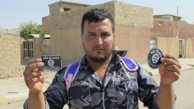 An Iraqi soldier shows the badges of Islamist State militants after taking control of Sulaiman Pek village in the northwest of Tikrit city
