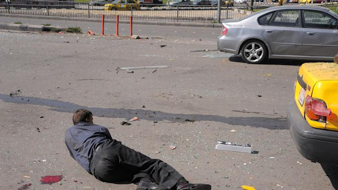 This photo released by the Syrian official news agency SANA shows an injured Syrian man lying on the ground after a huge explosion that shook central Damascus, Syria, Thursday, Feb. 21, 2013. A car bomb shook central Damascus on Thursday, exploding near the headquarters of the ruling Baath party and the Russian Embassy, eyewitnesses and opposition activists said. (AP Photo/SANA)