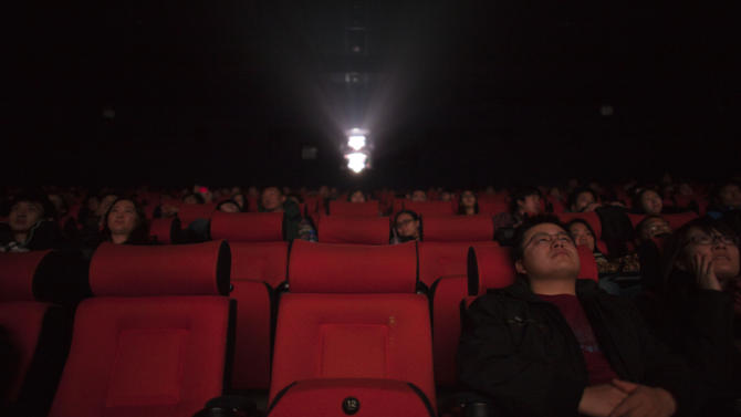 """FILE - In this Wednesday, Jan. 16, 2013 file photo, moviegoers and journalists watch the latest James Bond 007 movie series' """"Skyfall"""" during the movie's premier ceremony at a cinema in Beijing, China. Tens of millions of film fanatics are entering theaters around Asia during the long Lunar New Year holiday, but Hollywood can't count on them to boost the box office for its mostly serious Oscar nominees. Even with the Academy Awards buzz at a peak barely two weeks before the ceremony, patrons are opting for lighter fare. (AP Photo/Alexander F. Yuan, File)"""