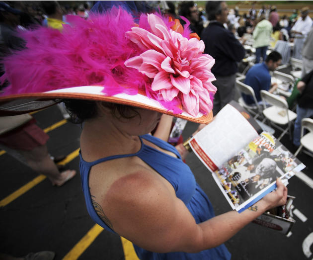 Lisa Scotti, of Baltimore, reads hhere program before the sixth race at Pimlico Race Course, Saturday, May 18, 2013, in Baltimore. The 138th Preakness Stakes horse race takes place Saturday. (AP Photo