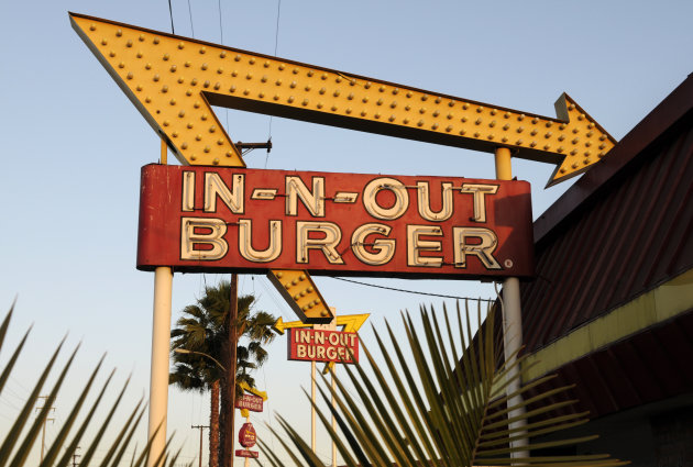 In-N-Out Burger signs from the fast food chain's original location, and one in the background at a new location across the Interstate 10 freeway, fill the skyline.