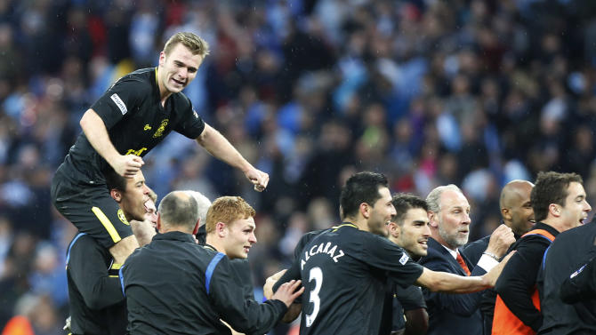 Wigan Athletic's players celebrate their win against Manchester City at the end of their English FA Cup final soccer match at Wembley Stadium, London, Saturday, May 11, 2013. (AP Photo/Jon Super)