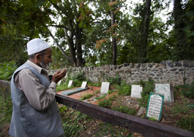 "A Kashmiri Muslim prays near an unmarked grave, right foreground, inside a martyrs graveyard in Srinagar, India, Wednesday, Sept. 5, 2012. The government of Kashmir has rejected wide-scale DNA testing of bodies in thousands of unmarked graves despite pleas by the families of those who disappeared during two decades of fighting in the restive region. The Tombstone reads, ""unidentified fifteen year old boy shot and killed by Border Security Force soldiers on 5th September 2003."" (AP Photo/ Dar Yasin)"