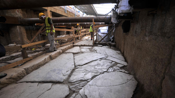 Workers of Metro's construction company are seen at the ancient ruins in the northern Greek port city of Thessaloniki on Monday, June 25, 2012. Archaeologists in Greece's second largest city have uncovered a 70-meter (230-foot) section of an ancient road built by the Romans that was city's main travel artery nearly 2,000 years ago. The marble-paved road was unearthed during excavations for the city's new subway system that is due to be completed in four years, and will be raised to be put on permanent display for passengers when the metro opens. (AP Photo/Nikolas Giakoumidis)