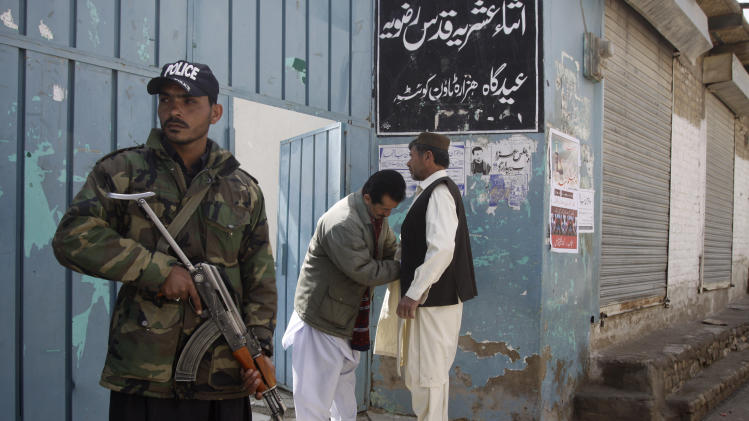 """In this Friday, Feb. 22, 2013, photo, a Pakistani security man stands guard outside a mosque in Quetta, Pakistan. Pakistan's minority Shiite Muslims have begun to use words like """"genocide"""" to describe a violent spike in attacks directed against them by a militant Sunni group, with suspicious links to the country's security agencies and a mainstream political party that governs the largest province, where some of the most violent jihadi groups are headquartered. (AP Photo/Arshad Butt)"""