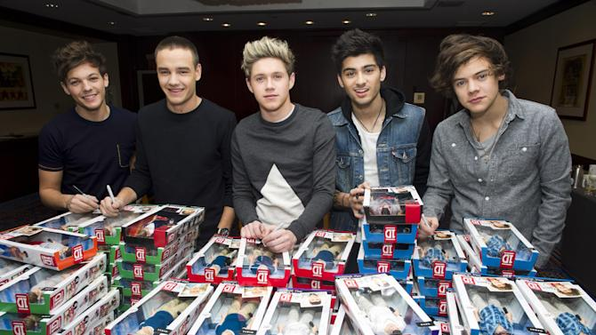 Members of worldwide musical sensation One Direction, from left to right, Louis Tomlinson, Liam Payne, Niall Horan, Zayn Malik and Harry Styles sign boxes of their Hasbro dolls at a press event on Monday, Nov. 26, 2012 in New York. (Photo by Charles Sykes/Invision for Hasbro/AP Images)