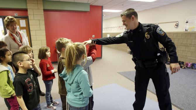 In a photo made Thursday, Feb. 21, 2013, police officer Jeff Strack kids around with  children at Jordan Elementary School in Jordan, Minn. In what is believed to be the first of its kind nationwide, the small city south of Minneapolis is taking school security to a new level by setting up satellite offices inside the public school buildings. (AP Photo/Jim Mone)