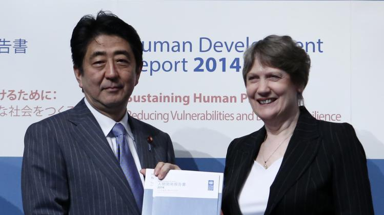 Japan's PM Abe poses for photos with UNDP Administrator Clark during announcement event of Global Launch of Human Development Report 2014 at the United Nations University Headquarters in Tokyo
