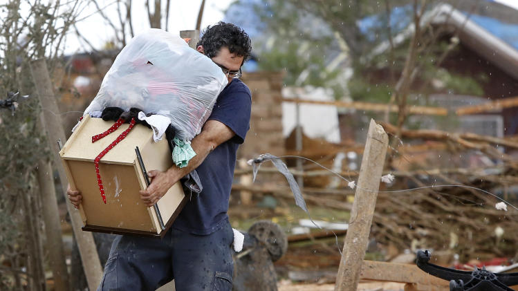 A man carries a drawer and a bag filled with clothes from Rachel Hernandez' home as residents of the Heatherwood Addition, on the south side of SE 4 and Bryant in Moore, Okla.,  returned to their homes Tuesday, May 21, 2013, to salvage any items after Monday's destructive tornado. (AP Photo/The Oklahoman, Jim Beckel)