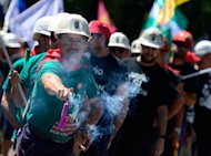 A Spanish coal miner holds a firecracker during a demonstration on July 11, in Madrid, in protest at industry subsidy cuts that they say threaten their communities