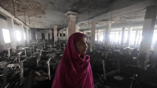 Bangladeshi garment worker Shahinur looks inside the damaged Smart Export Garment Ltd. factory where a fire Saturday claimed the lives of seven of her female colleagues in Dhaka, Bangladesh, Sunday, Jan. 27, 2013. Bangladesh's government has ordered an investigation into allegations that the sole emergency exit at the factory was locked, an official said Sunday. Saturday's fire occurred just two months after a blaze killed 112 workers in another factory near the capital, raising questions about safety in Bangladesh's garment industry, which exports clothes to leading Western retailers. (AP Photo/A.M. Ahad)