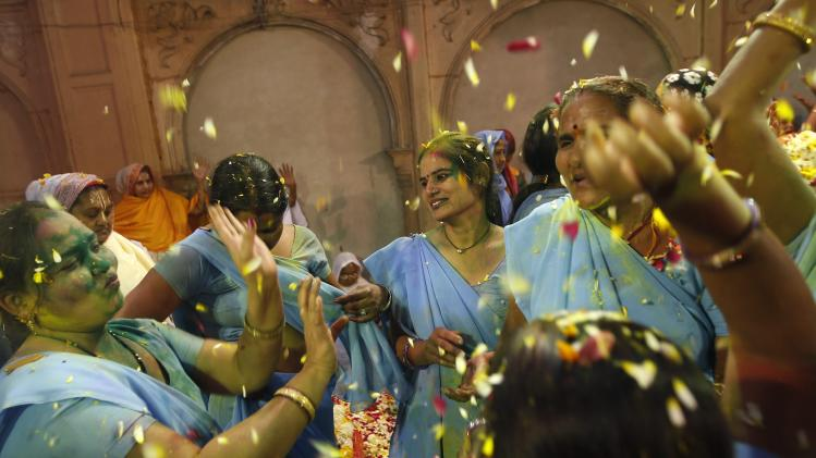 Women, who are former scavengers, throw flowers into the air during the Holi celebrations in Vrindavan
