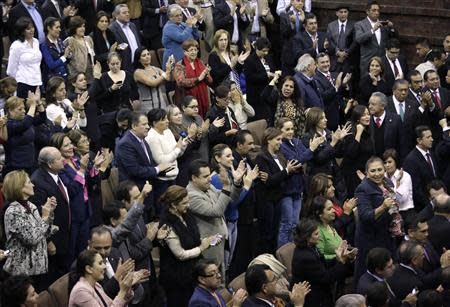 Mexican congressmen applaud after Mexico Congress approves the biggest oil sector shake-up in the lower house in Mexico City