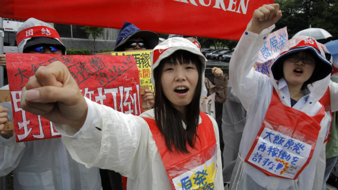 "Demonstrators raise clenched fists during a rally, protesting against restarting the Ohi nuclear power plant's reactors in front of the prime minister's official residence in Tokyo, Saturday, June 16, 2012. Japan moved closer to restarting the nuclear reactors for the first time since last year's earthquake and tsunami led to a nationwide shutdown. A slogan, center, reads: ""Stop restarting nuclear power plant."" (AP Photo/Itsuo Inouye)"