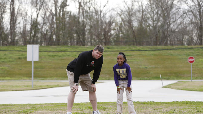 Former NFL football player Jon Stinchcomb, left, gives a Emily C. Watkins Elementary student advice during the NFLPA One Team One Community event at Emily C. Watkins Elementary School on Wednesday January 30, 2013 in LaPlace, Louisiana. (Aaron M. Sprecher/AP Images for NFLPA)