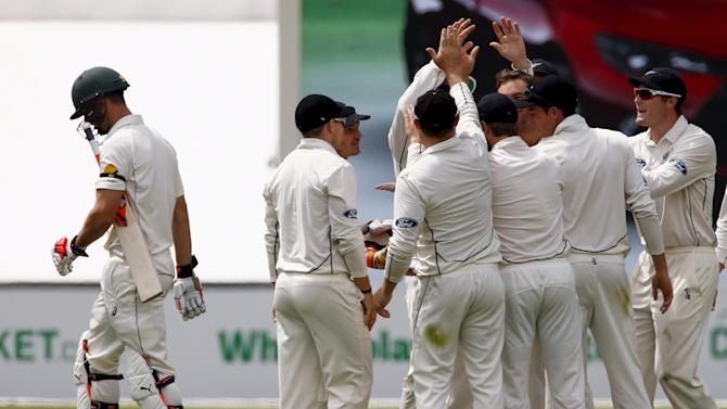 Australia's Marsh walks off the ground as New Zealand players celebrate his dismissal for four runs during the second day of the third cricket test match at the Adelaide Oval, in South Australia