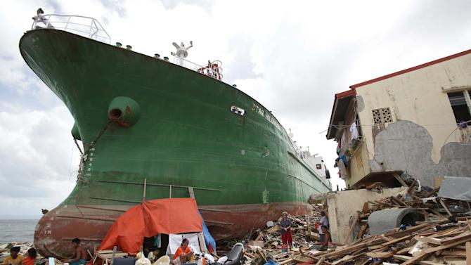 Survivors stay beside a ship that was washed ashore hitting makeshift houses near an oil depot in Tacloban city, Leyte province central Philippines on Monday, Nov. 11, 2013. Authorities said at least 2 million people in 41 provinces had been affected by Friday's typhoon Haiyan and at least 23,000 houses had been damaged or destroyed. (AP Photo/Aaron Favila)