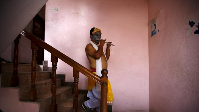 A reveller depicting as Lord Krishna, a Hindu deity, walks down the stairs to take part in a LGBT pride parade in Kathmandu