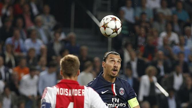 PSG's Zlatan Ibrahimovic heads the ball ahead of Ajax's Niklas Moisander during the Group F Champions League match between Ajax and Paris Saint-Germain at ArenA stadium in Amsterdam, Netherlands, Wednesday, Sept. 17, 2014. (AP Photo/Peter Dejong)