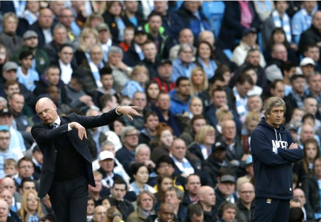 Wigan Athletic manager Rosler and his Manchester City counterpart Pellegrini react during their English FA Cup quarter final match in Manchester