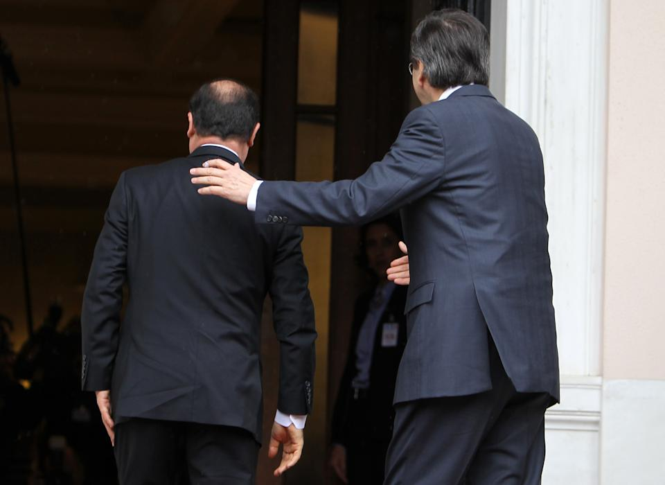 Greece's Prime Minister Antonis Samaras, right, and French President Francois Hollande enter Maximos mansion in Athens, Tuesday, Feb. 19, 2013. Hollande arrived in Athens Tuesday for a brief visit of little more than six hours, with talks to focus on Greece's deep financial crisis. (AP Photo/Thanassis Stavrakis)