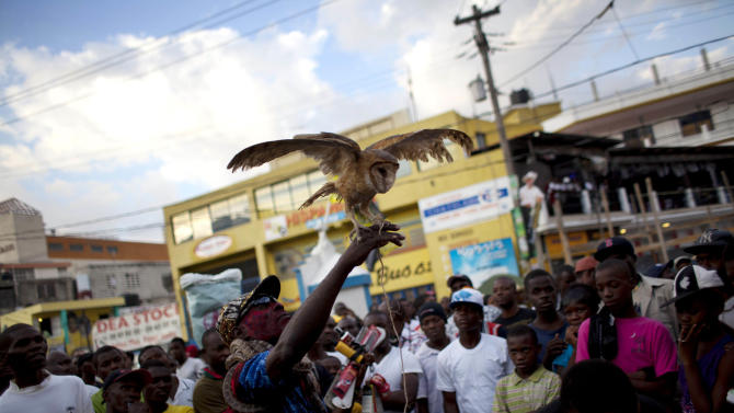 In this Jan. 27, 2013 photo, snake handler Saintilus Resilus performs with an owl he caught in the wild just days before as he performs during pre-Lenten Carnival season  in Petionville, Haiti. This year, Resilus has new catches to display: an owl that he promises to let them go after Carnival.  (AP Photo/Dieu Nalio Chery)