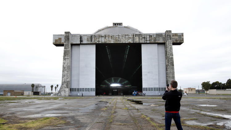 Bradley Hasemeyer, the host of AOL's Trasnlogic show, uses his smartphone to photograph the Aeroscraft airship, a high-tech prototype airship, outside a World War II-era hangar in Tustin, Calif., Thursday, Jan. 24, 2013. Work is almost done on a 230-foot rigid airship inside the blimp hangar at a former military base in Orange Co. The huge cargo-carrying airship is has shiny aluminum skin and a rigid, 230-foot aluminum and carbon fiber skeleton. (AP Photo/Jae C. Hong)