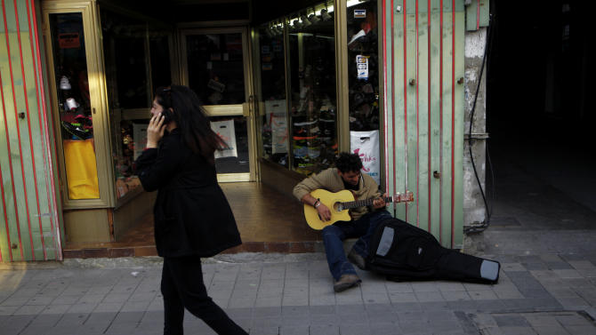 A man plays with his guitar as a woman passes at  Ledras street in Nicosia, Cyprus, Saturday, March 23, 2013. Politicians in Cyprus were racing Saturday to complete an alternative plan raising funds necessary for the country to qualify for an international bailout, with a potential bankruptcy just three days away. (AP Photo/Petros Karadjias)