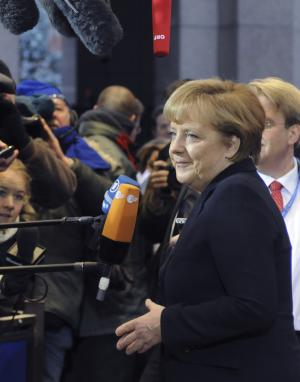 German Chancellor Angela Merkel, right, speaks with the media as she arrives for an EU summit in Brussels, Friday, Dec. 17, 2010. European Union leaders are changing the treaty that underpins the bloc to make room for a huge new rescue system for countries that get into debt trouble in the long term. (AP Photo/Thierry Charlier)