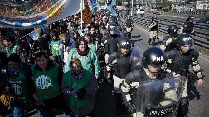 Riot police cordon off protesters partially blocking one of Buenos Aires' main access routes over the Riachuelo River in Argentina, Wednesday, Aug. 27, 2014. CTA, a union umbrella group that opposes the government, started a 36-hour strike to demand more jobs, better salaries and tax cuts on salaries. (AP Photo/Victor R. Caivano)