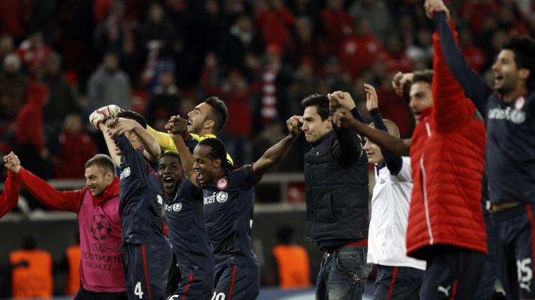 Olympiakos' players celebrate after beating Anderlecht in their Champions League soccer match at Karaiskaki stadium in Piraeus