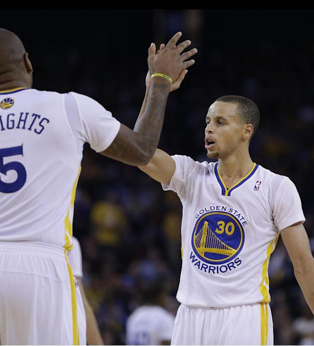 Golden State Warriors' Stephen Curry, right, is congratulated by Marreese Speights after Curry scored against the Los Angeles Lakers during the second half of an NBA basketball game, Saturday, Dec
