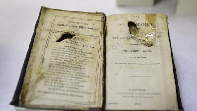"""The bible belonging to Confederate soldier C. Robey, who was wounded on the third day of Gettysburg battle, is prepared for display in a work room at the museum of the Confederacy in Richmond, Va., Wednesday, May 1, 2013. The Museum of the Confederacy will open the exhibit """"Gettysburg: They walked through blood"""" on May 11 to commemorate the 150th anniversary of the Battle of Gettysburg. (AP Photo/Steve Helber)"""