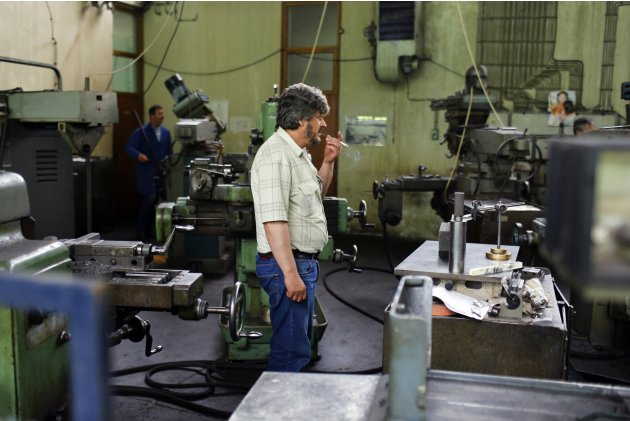 "A worker smokes a cigarette at the manufacturing hall in the ""Zastava Arms"" weapons factory in the Serbian town of Kragujevac"