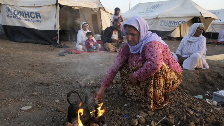 A woman from minority Yazidi sect, who fled violence in Iraqi town of Sinjar, makes tea at Bajed Kadal refugee camp, southwest of Dohuk province