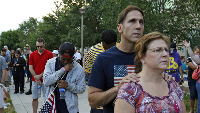 """Crowd members pray, Sunday, July 22, 2012, in Aurora, Colo., during a prayer vigil for the victims of Friday's mass shooting at a movie theater. Twelve people were killed and dozens were injured in a shooting attack Friday at the packed theater during a showing of the Batman movie, """"The Dark Knight Rises."""" Police have identified the suspected shooter as James Holmes, 24. (AP Photo/Alex Brandon)"""