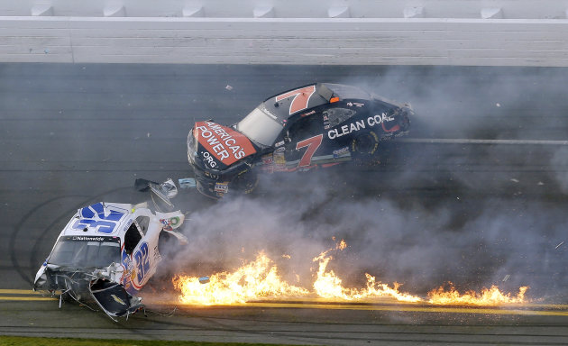 Kyle Larson's car is on fire as he slides down the track with Regan Smith after being involved in a crash at the conclusion of the NASCAR Nationwide Series auto race Saturday, Feb. 23, 2013, at Dayton