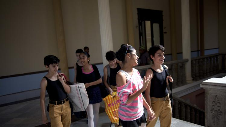 In this April 3, 2013 photo, identical triplets Marcos, Cesar, and Angel Ramirez Castellanos walk with fellow ballet students before class at the National School of Ballet in Havana, Cuba.  The Ramirez brothers spend 12 hours a day at the National School of Ballet, housed in a graceful building that occupies a full half-block in colonial Old Havana. Classes include not only dance, but also subjects like language, math and history. (AP Photo/Ramon Espinosa)