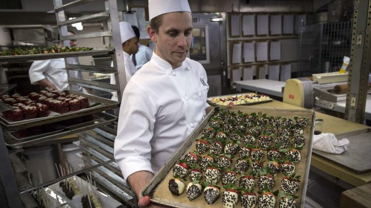 Pastry Sous Chef Michael Ottomanelli holds chocolate-dipped strawberries covered in larvae in the kitchen before the 110th Explorers Club Annual Dinner at the Waldorf Astoria in New York