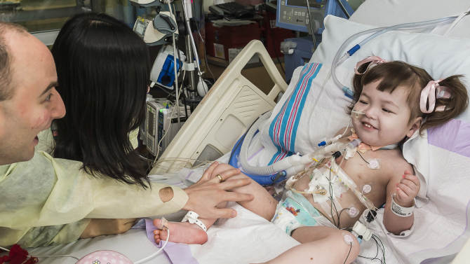 In this April 26, 2013 photo provided by OSF Saint Francis Medical Center in Peoria, Ill., Darryl Warren and Lee Young-mi visit their 2-year-old daughter, Hannah Warren, in a post-op room at the Children's Hospital of Illinois in Peoria after having received a new windpipe in a landmark transplant operation on April 9, 2013. Hannah was born in South Korea without a windpipe but received a new one made from her own stem cells. She is the youngest patient ever to get the experimental treatment. Doctors announced Tuesday, April 30, 2013 she is recovering and likely will lead a normal life. (AP Photo/OSF Saint Francis Medical Center, Jim Carlson)